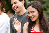 Portrait young happy teenage girl at the park with friends — Stock Photo