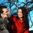 Happy young couple on park with cellphone — Stock Photo