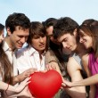 Group of young guys and girls with a sphere in the form of hear — Stock Photo
