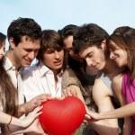 Groupe de jeunes mecs et les filles avec une sphère sous la forme d'entendre — Photo