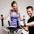 Stock Photo: Girl on training apparatus and instructor in sportclub