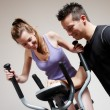 Girl on training apparatus and instructor in sportclub — Stock Photo