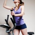 Girl on training apparatus drinks water in sportclub — Stock Photo