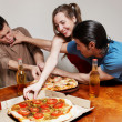 The cheerful company of youth eating a pizza — Stock Photo