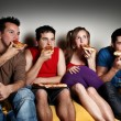 The concentrated fans with a pizza in hands, watching TV - Stock Photo