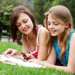Two girlfriends in park with a mobile phone — Stock Photo #6404818