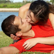 Happy young couple kissing at park in grass — Stock Photo