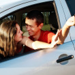 Happy young pair in just bought car — Stock Photo