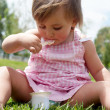 The little girl eats yoghurt sitting on a grass — Stock Photo