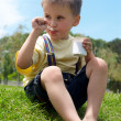 The little boy is appetizing eats yoghurt sitting on a grass in — Stock Photo