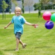 Stock Photo: The little boy running on a grass with balloons