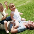 Happy mother playing with children on a lawn — Stock Photo