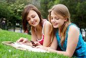 Due amiche nel parco con un telefono cellulare — Foto Stock