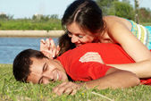 Happy young couple playing at park in grass — Stock Photo