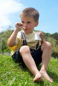 Malý chlapec je chutný sní jogurt sedět na trávě v — Stock fotografie
