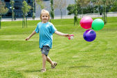 The little boy running on a grass with balloons — Stock Photo