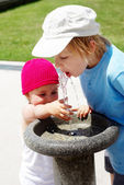 Children drinking water in a drinking fountain in park — Stock Photo
