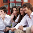 Group of young guys and girls sitting together — Stock Photo