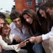 Happy young group on street with cellphone — Stock Photo #6440913