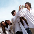 Group of young men stretching hands to a bottle with water — Stock Photo #6440961