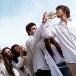 Groupe de jeunes hommes qui s'étend de mains pour une bouteille avec de l'eau — Photo