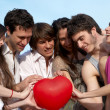 Foto Stock: Group of young guys and girls with a sphere in the form of heart