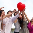 Group of young guys and girls with a sphere in the form of heart — 图库照片