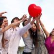 Group of young guys and girls with a sphere in the form of heart — Stock fotografie