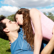 Happy young couple kissing at park in grass — Stock Photo #6442412