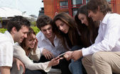 Happy young group on street with cellphone — Stock Photo