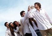 Grupo de jóvenes, estirando las manos a una botella con agua — Foto de Stock