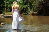 The young girl in white going on river — Stock Photo