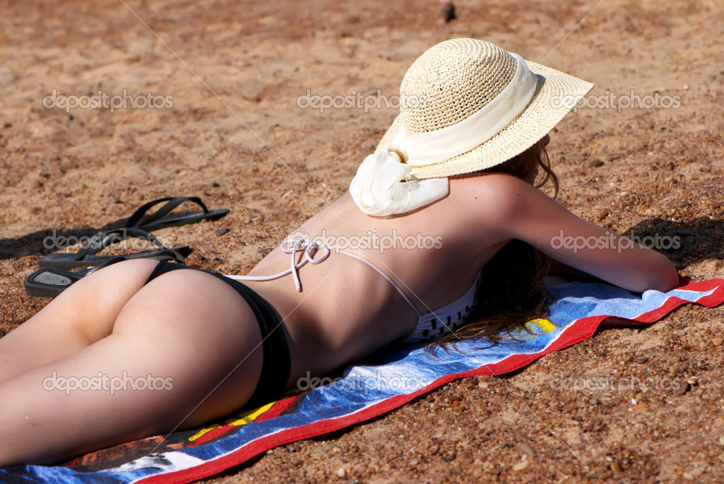 Woman in hat lies on the beach  Stock Photo #6442673