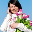 Portrait happy women with pink tulips talking by a cellular tele — Stock Photo