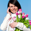 Portrait happy women with pink tulips talking by a cellular tele — Stock Photo #6668441