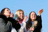 Belos amigos soprando bolhas na natureza — Fotografia Stock