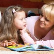 Sweet  little girl with mother reading book — Stock Photo