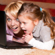 Photo: Picture of happy mother and child with laptop computer