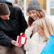 Happy friends with a New Year's gift in the street — Stock Photo