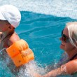 Smiling beautiful woman and little boy bathes in pool - Stockfoto