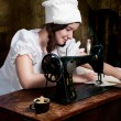 Stock Photo: Portrait of a young seamstress with old sewing machine