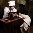 Portrait of a young seamstress with old sewing machine — Stock Photo