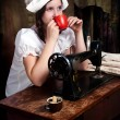 Portrait of a young seamstress with red mug near old sewing mach - Stock Photo