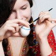 Stock Photo: Portrait of a young girl who is painting an egg for easter