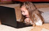 Retrato de una niña con un ordenador portátil — Foto de Stock