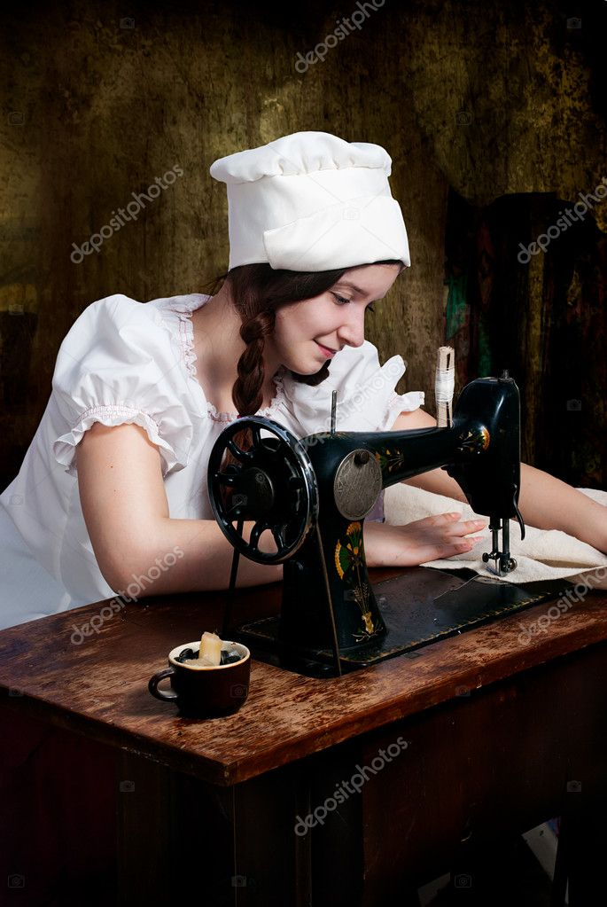 Portrait of a young seamstress with old sewing machine — Stock Photo #6685605