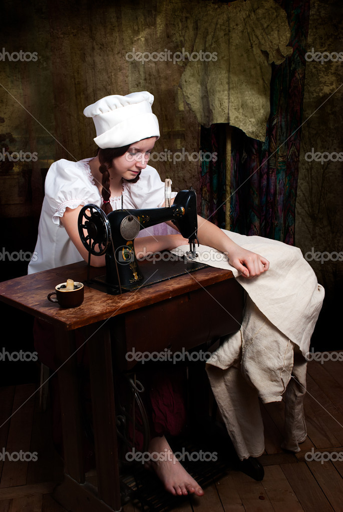 Portrait of a young seamstress with old sewing machine — Stock Photo #6685607