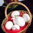 Basket full of easter eggs with spring flower — Stock Photo