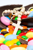 Cross worn on the neck against easter chocolate egg and sweets — Stock Photo