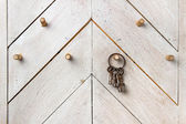Set of old keys hanging on wooden wall — Stock Photo